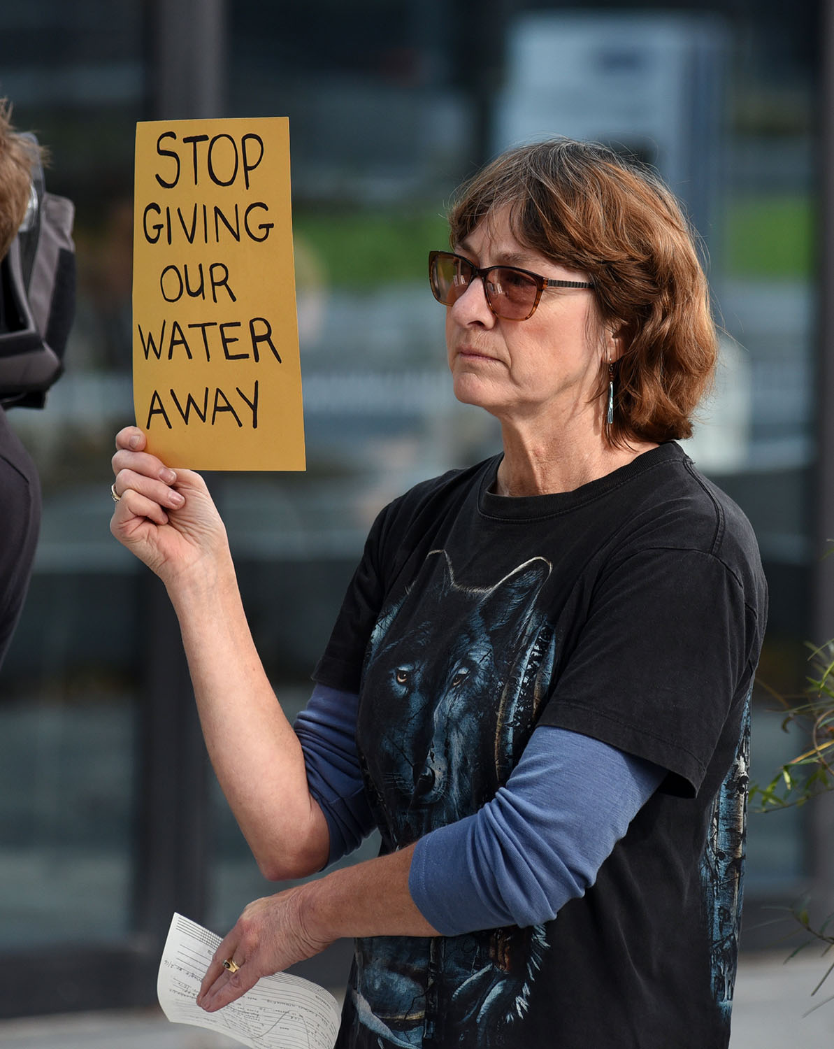 """Disgruntled anti-water bottling protester holds up a sign reading, """"Stop giving our water away."""""""